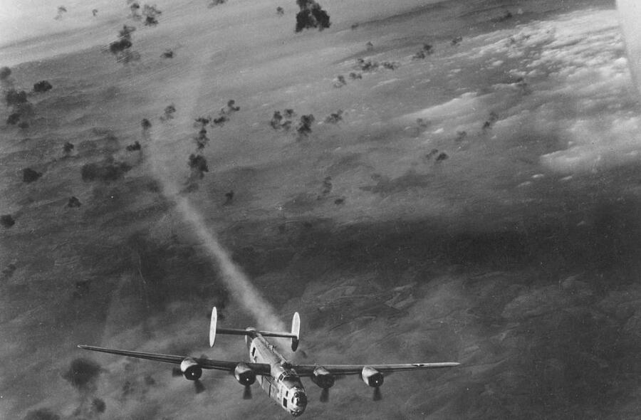 Бомбардировщик B-24 выныривает из облака разрывов снарядов зенитных орудий с дымящимся двигателем