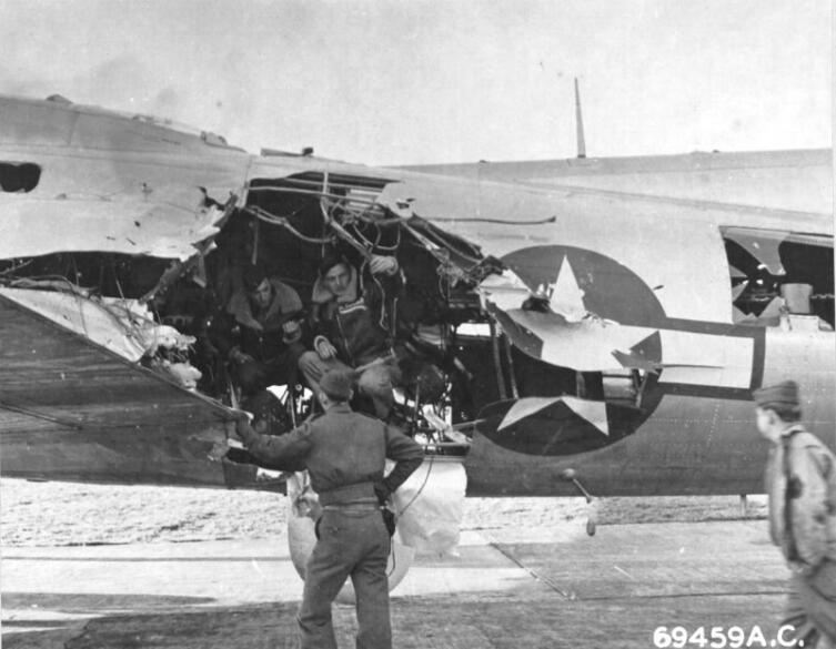 Экипаж американского бомбардировщика B-17 осматривает повреждения своего самолета после налета на Мюнхен
