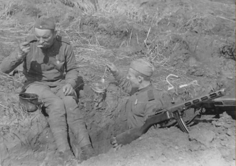 Расчет советских бронебойщиков принимает пищу в окопе