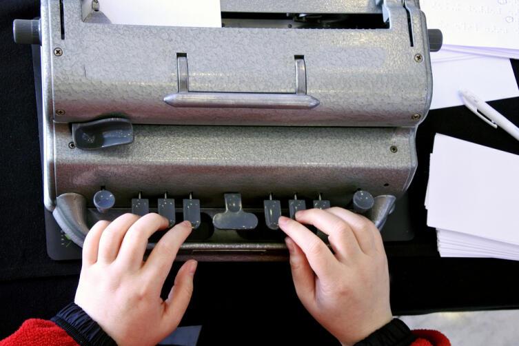 Слепой человек печатает на машинке Брайля