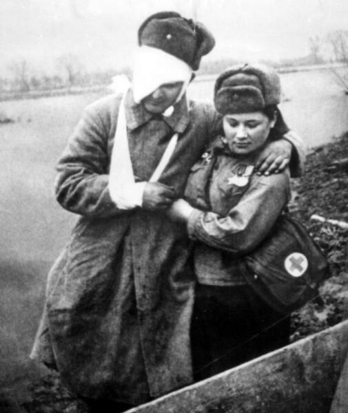 Санинструктор М. С. Нечепорчукова оказывает помощь раненному командиру пулемётного расчёта А. С. Рогачёву