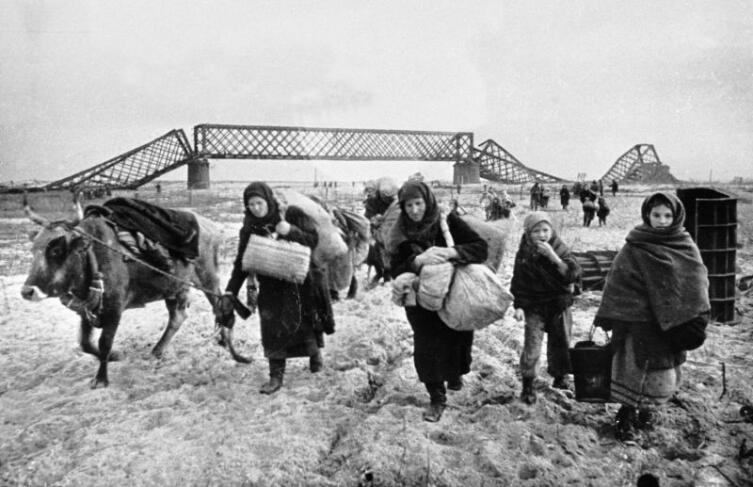 Советские беженцы идут у разрушенного железного моста, покидая родные места