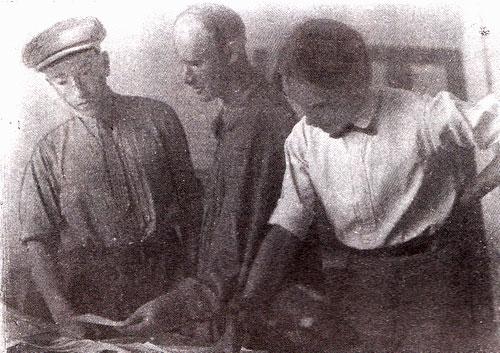 Н. Ладовский (в центре) студентами И. Иозефовичем (в кепке) и В. Поповым просматривает фотографии