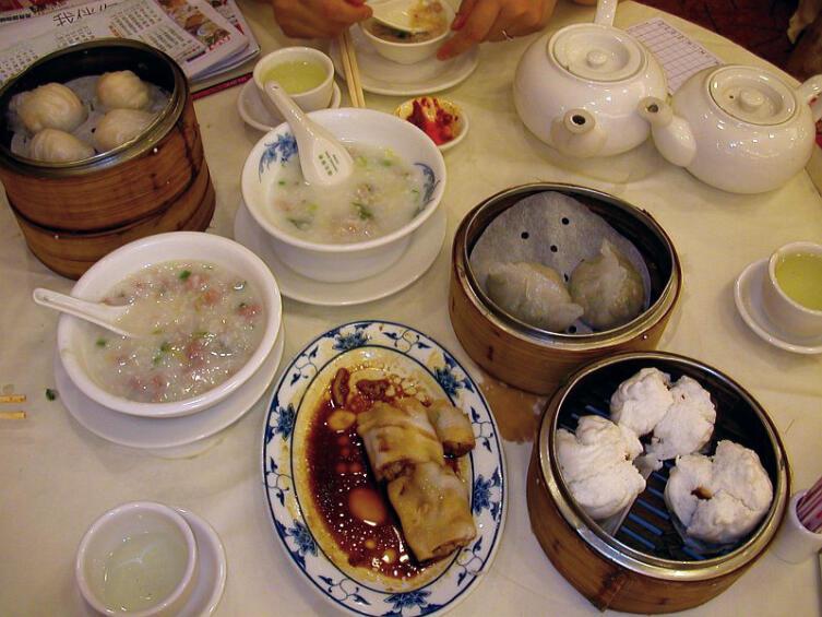 Типичный «дим сам»-завтрак в Гонконге. Слева направо и сверху вниз: креветочные шарики (ха гау), жасминовый чай, курица с овощами, рисовый суп (две чашки с ложками), приготовленная на пару лапша (слева), рисовая лапша с соевым соусом (на тарелке), подогретые на пару булочки со свининой
