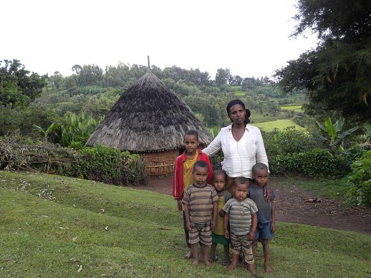 Африканская семья и тукул на заднем фоне