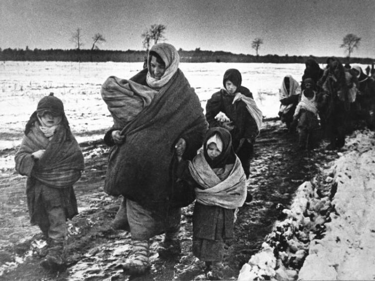 Советские женщины и дети возвращаются домой. Авторское название фото — «В родное село», 1943 г.