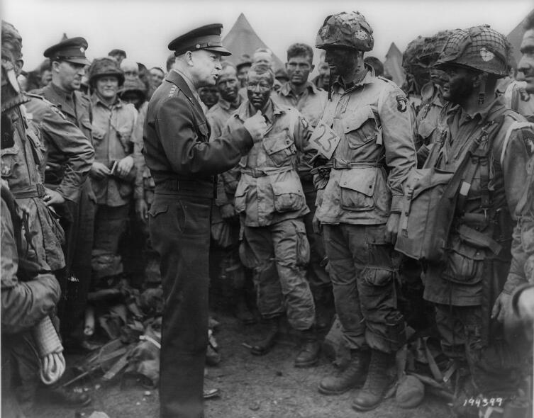 Верховный Главнокомандующий союзными войсками в Европе генерал Эйзенхауэр ведёт беседу с десантниками роты «Е» 502-го парашютно-десантного полка[en] перед началом воздушно-десантной операции в Нормандии. 5 июня 1944 г.