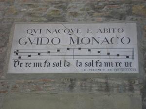 Мемориальная доска в Ареццо на улице Рикасолли на доме, в котором родился Гвидо.  На ней изображены квадратные ноты.