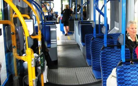 В трамвае. На желтых поручнях кнопки открытия дверей, в конце вагона кабинка кондуктора